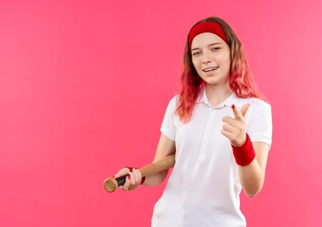 Junge sportliche frau im stirnband hält fledermaus, der mit dem finger zur kamera zeigt, die fröhlich über rosa wand stehend lächelt