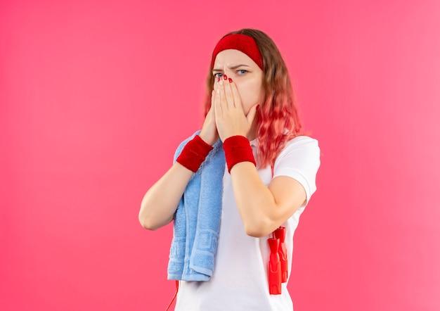 Junge sportliche frau im stirnband mit handtuch auf der schulter schockiert, mund mit händen bedeckend, die über rosa wand stehen
