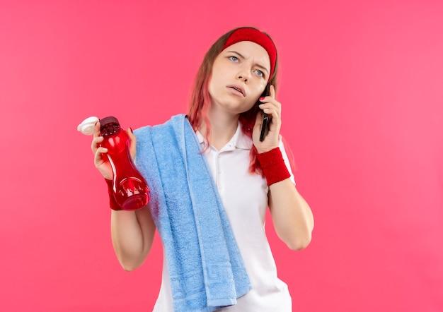 Junge sportliche frau im stirnband mit handtuch auf schulter, die flasche wasser hält, während auf monilem telefon mit ernstem gesicht steht, das über rosa wand steht