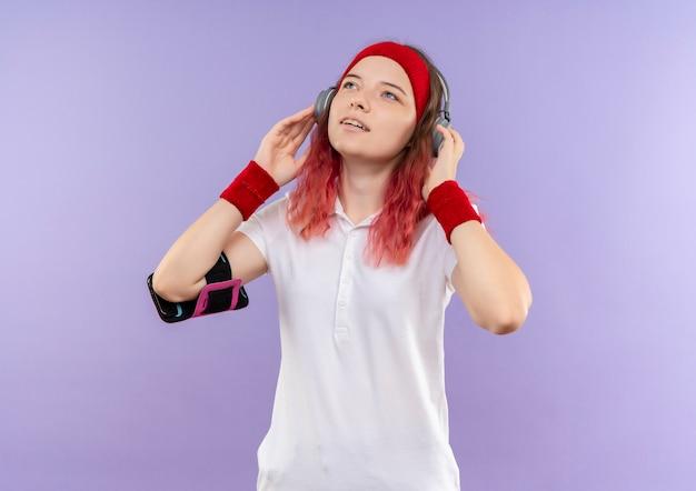 Junge sportliche frau im stirnband mit kopfhörern, die nach oben schauen, genießen ihre lieblingsmusik, training mit smartphone-armbinde stehend über lila wand