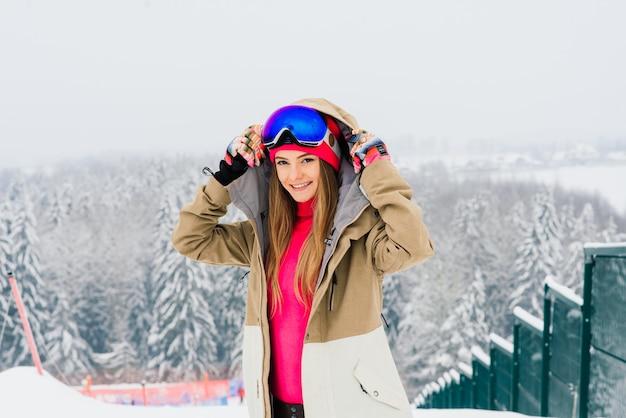 Junge sportliche frau im winter mit snowboard, brille