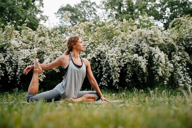 Junge sportliche frau in leggings führt yoga-übungen im horizontalen kopienraum des frischen luftsportbanners durch