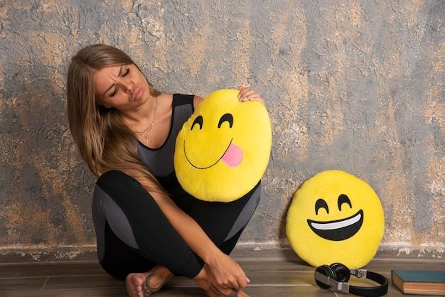 Junge sportliche frau in sportoutfits, die ein lächelndes und zunge heraus emoji-kissen halten