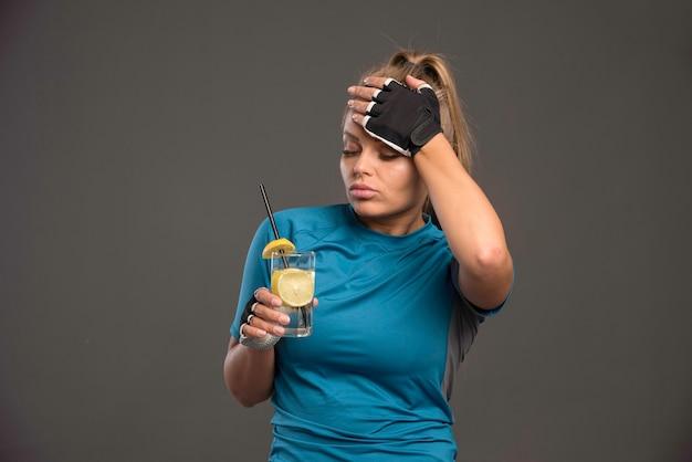 Junge sportliche frau ist müde und trinkt wasser mit zitrone.
