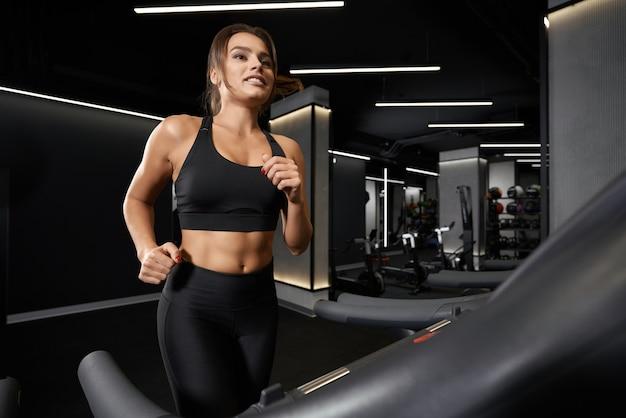 Junge sportliche frau macht cardio auf laufband tread