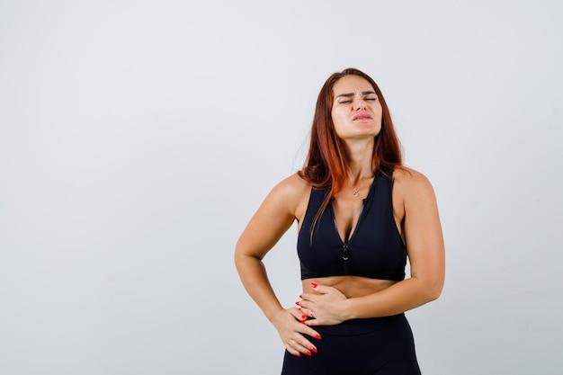 Junge sportliche frau mit bauchschmerzen