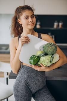 Junge sportliche frau mit schuppen und gemüse an der küche