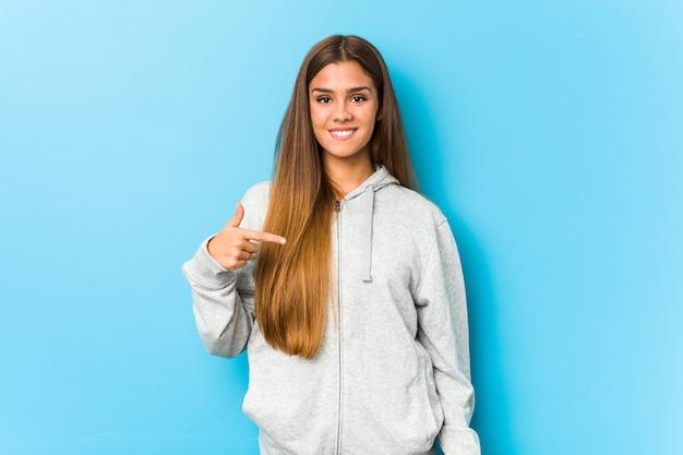 Junge sportliche frau person, die von hand auf einen hemdkopierraum zeigt, stolz und zuversichtlich