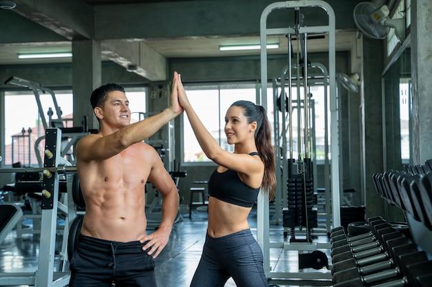Junge sportliche frau und mann, die einander eine hohe fünf nach dem training im fitnessstudio, fitnessübung und gesundem konzept geben.