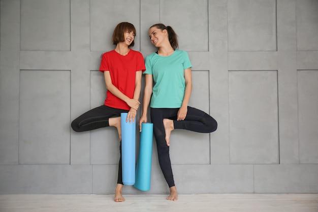 Junge sportliche frauen mit yogamatten nahe grauer wand