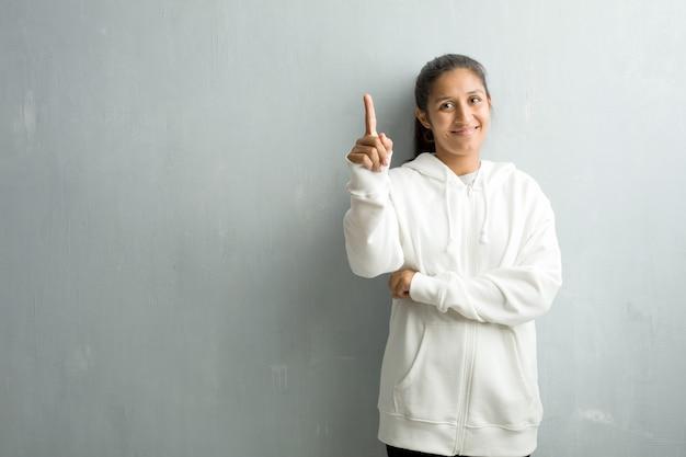 Junge sportliche indische frau gegen eine turnhallenwand, die nummer eins, symbol der zählung zeigt