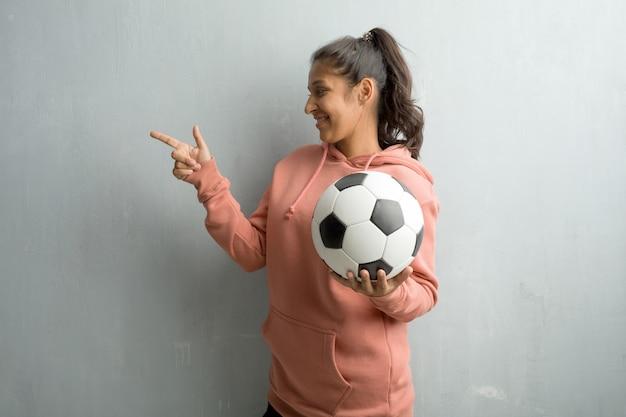 Junge sportliche indische frau gegen eine wand, die auf die seite zeigt