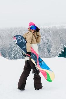 Junge sportliche lächelnde frau im winter mit snowboard, brille