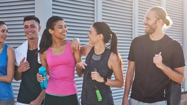Junge sportliche leute unterhalten sich glücklich, während sie ins fitnessstudio gehen