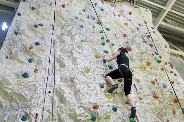Junge sportliche mädchen, die klettern üben.