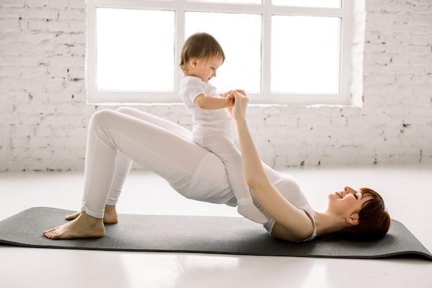 Junge sportliche mutter macht körperliche yoga oder pilates-übungen, hintern brücke, zusammen mit ihrem baby vor großen fenstern hintergrund. fitness, glückliche mutterschaft