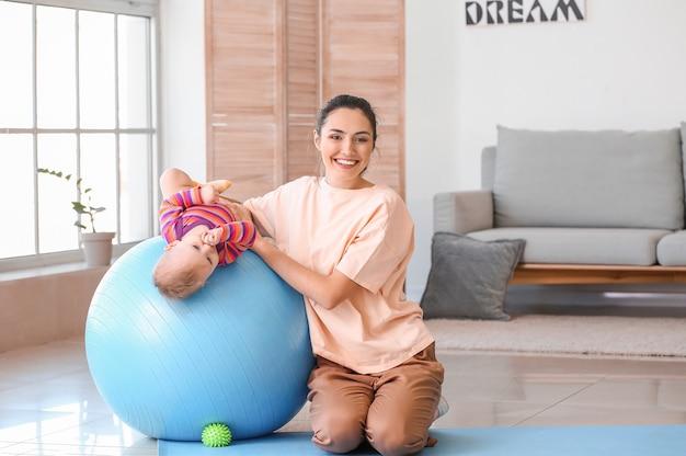 Junge sportliche mutter und ihr baby, die übungen mit fitball zu hause machen