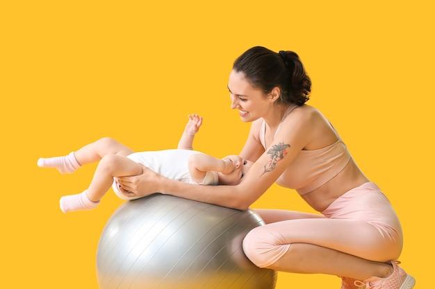 Junge sportliche mutter und ihr baby machen übungen mit fitball auf gelb