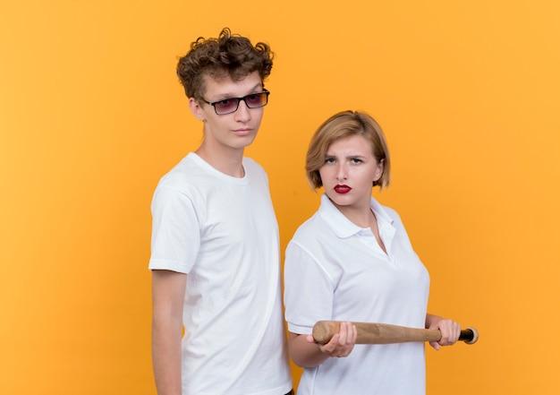 Junge sportliche paarfrau mit baseballschläger, der neben ihrem freund mit ernstem gesicht steht über orange wand steht
