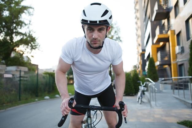 Junge sportliche radfahrer mit fahrradhelm, fahrrad fahren, selbstbewusst in die kamera schauen