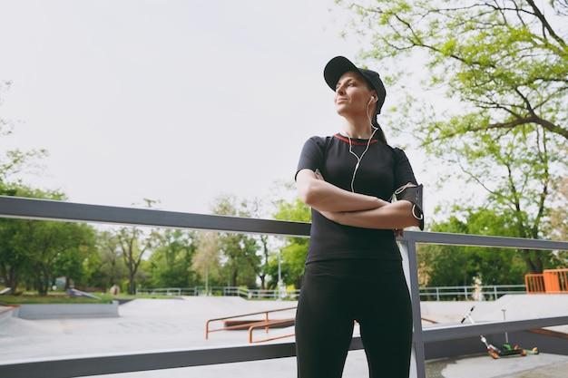 Junge sportliche schöne frau in schwarzer uniform, mütze mit kopfhörern, die musik hören, stehend die hände vor oder nach dem laufen gefaltet halten, im stadtpark im freien trainieren