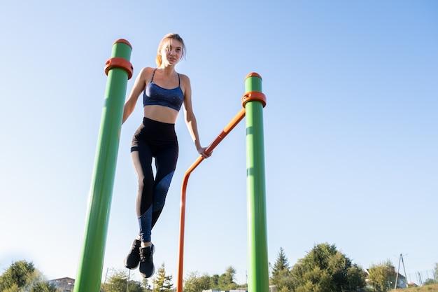 Junge sportliche sportlerin, die fitnessübung auf metallstangen im freien am stadionplatz tut.