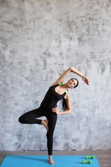 Junge sportliche sportliche schlanke frau, die übung im fitnessstudio tut.