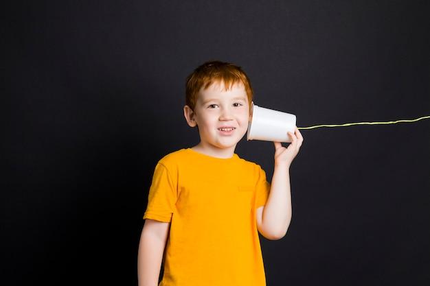 Junge spricht auf einem einfachen hausgemachten telefon
