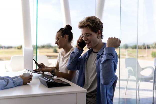 Junge spricht mit seinem handy mit einem zufriedenen ausdruck und einer geste an einem arbeitstisch mit anderen leuten in einem coworking