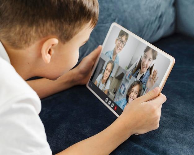 Junge spricht mit seinen freunden auf einem tablet per videoanruf