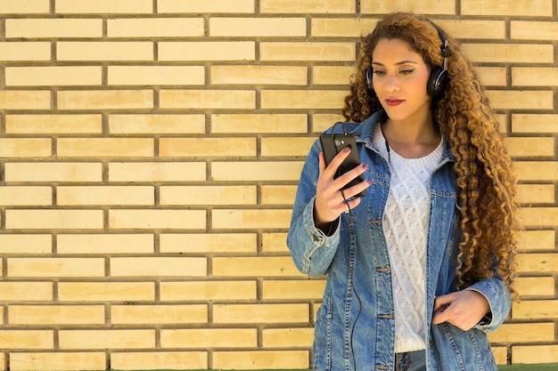 Junge städtische frau mit smartphone vor backsteinmauer