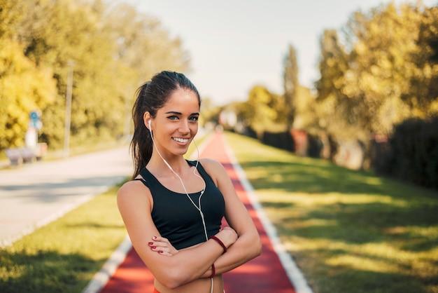 Junge städtische läuferfrau mit kopfhörern auf schottenstoffbahn. kamera betrachten.