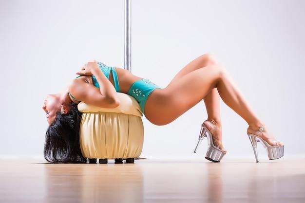 Junge stangentanzfrau, die gymnastik gegen einen weißen hintergrund tut