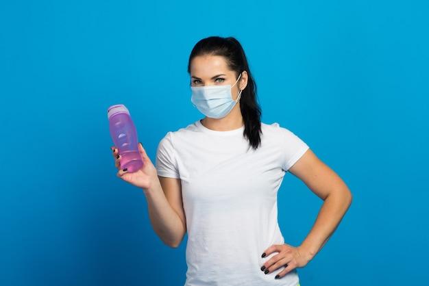 Junge starke fitnessfrau in einer gesichtsmaske, die auf blauem wandhintergrundstudio herausarbeitet.
