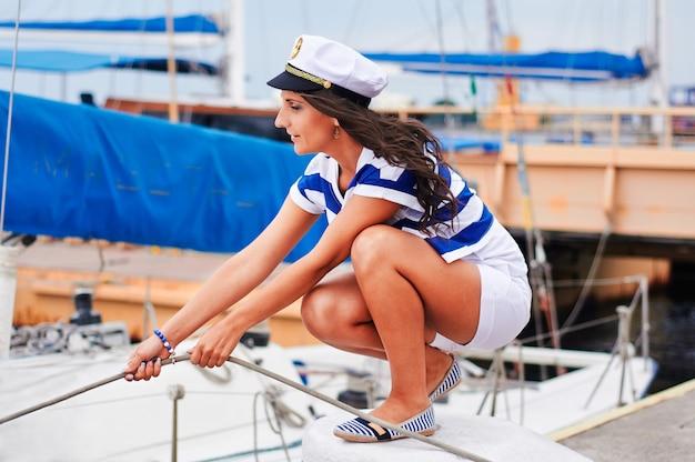 Junge starke frau, die das boot, seeart im hafen segelt