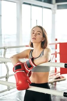 Junge starke frau in den roten boxhandschuhen, die durch bars der sportbahn stehen und ruhe nach hartem training im freizeitzentrum oder im fitnessstudio haben