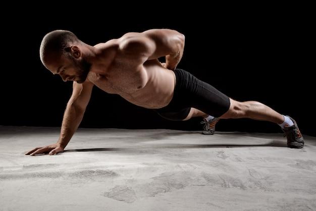 Junge starke sportler trainieren liegestütze über dunkle wand.