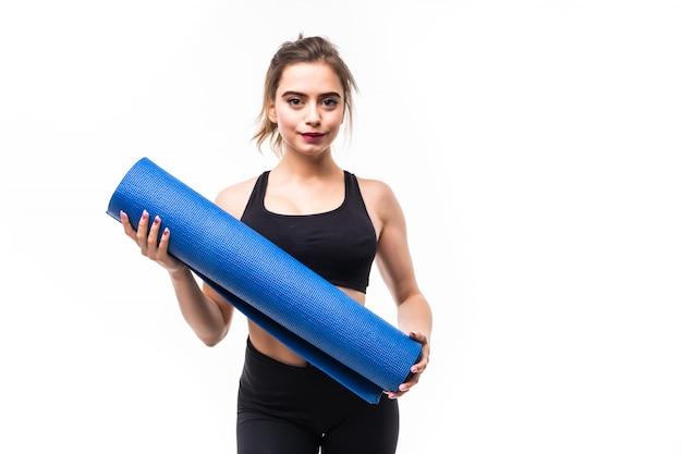 Junge starke sportlerin, die yoga auf einer matte praktiziert.
