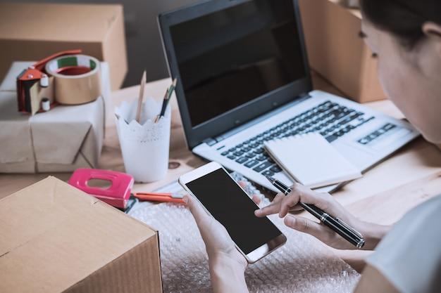 Junge starterunternehmerfrau, die zu hause mit intelligentem telefon arbeitet