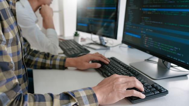 Junge startup-programmierer, die an schreibtischen sitzen und auf computern arbeiten, entwickeln programmierung und codierung, um eine lösung für das problem in der neuen anwendung zu finden