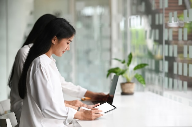 Junge startup-unternehmensgruppe, die als team arbeitet, um eine problemlösung zu finden und ein tablet mit weißem bildschirm zu verwenden.
