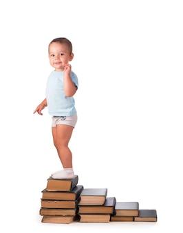 Junge steht auf einem stapel bücher für pädagogisches porträt - isoliert über weißer oberfläche