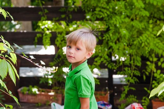 Junge steht im grünen garten