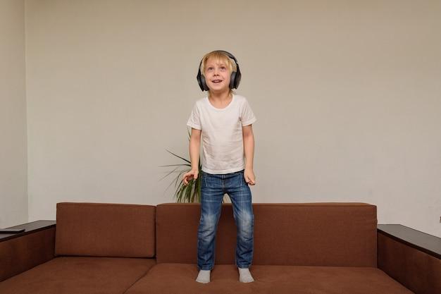 Junge steht in kopfhörern auf der couch. kind hört musik und tänze