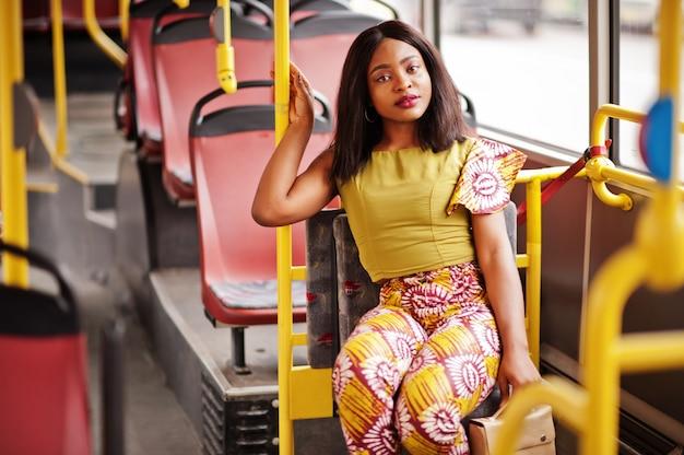 Junge stilvolle afroamerikanerfrau, die auf einem bus reitet.