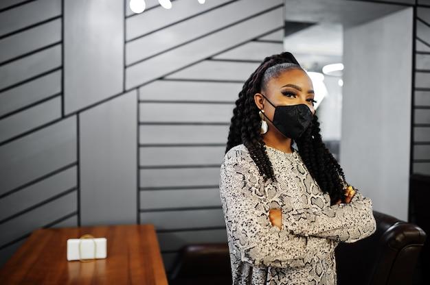 Junge stilvolle afroamerikanerfrau, die schwarze gesichtsmaskenhaltung innen trägt.