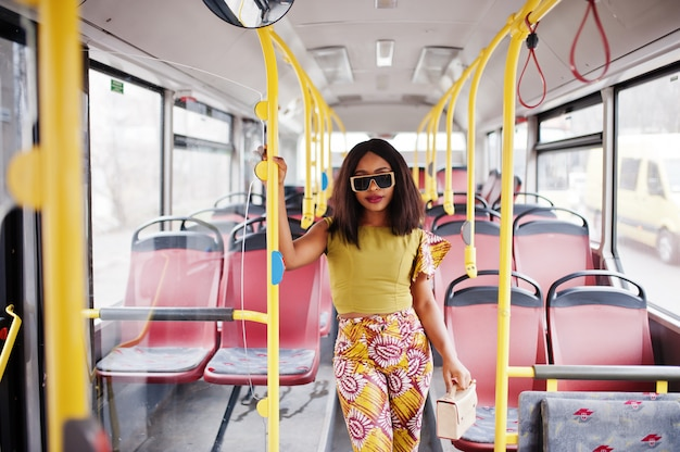 Junge stilvolle afroamerikanerfrau in der modernen sonnenbrille, die auf einem bus reitet.