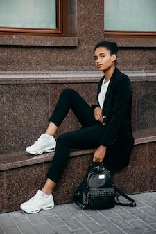Junge stilvolle afroamerikanische geschäftsfrau in der jacke, die auf treppen an der stadt sitzt und eine tasche hält.