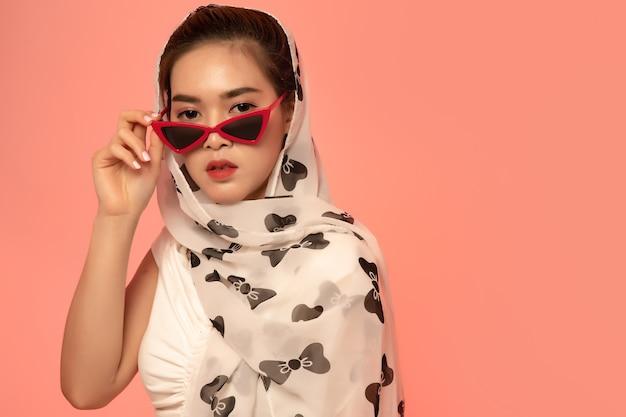 Junge stilvolle asiatische frau, die mit perlenhalskette aufwirft