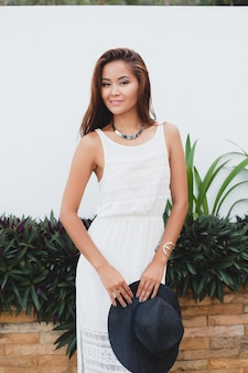 Junge stilvolle asiatische frau im weißen boho-kleid, vintage-stil, natürlich, lächelnd, glücklich, tropischer urlaub, hotel, honigmond